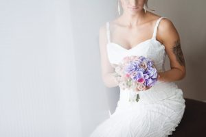 Bride in white sitting down holding a bouquet of flowers
