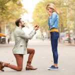 Man on one knee prosposing to a woman