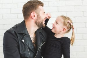 Man with tattoo having a laugh with his young daughter